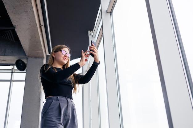 大きなガラス窓の前に立っているシャツとズボンを身に着けている彼女の携帯電話で忙しいプロの大人の実業家。