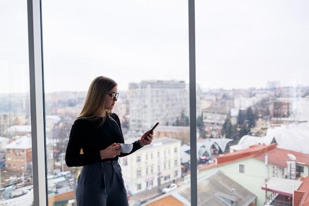 큰 유리창 앞에 서 있는 셔츠와 바지를 입고 휴대폰으로 문자 메시지를 보내는 전문 성인 여성