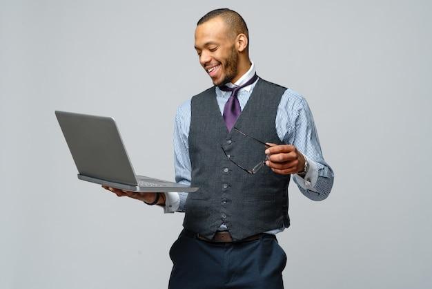 ラップトップコンピューターを保持しているプロのアフリカ系アメリカ人ビジネスの男性