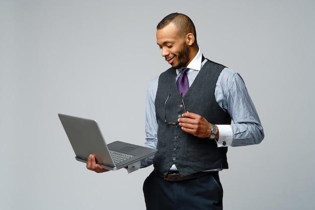 ラップトップコンピューターを保持しているプロのアフリカ系アメリカ人ビジネスの男性。