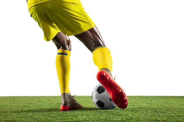 白いスタジオの背景に分離された動きの黄色いチームのプロのアフリカ系アメリカ人のフットボールまたはサッカー選手。行動、興奮、感情的な瞬間に人を合わせてください。ゲームプレイでの動きの概念。