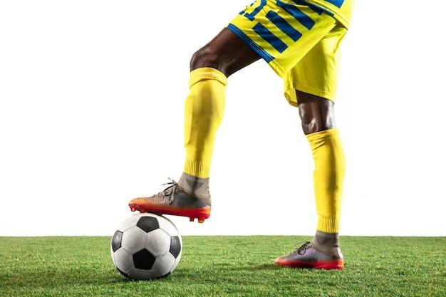 白いスタジオの背景に分離された動きの黄色いチームのプロのアフリカ系アメリカ人のサッカーまたはサッカー選手。行動、興奮、感情的な瞬間に人を合わせてください。ゲームプレイでの動きの概念。