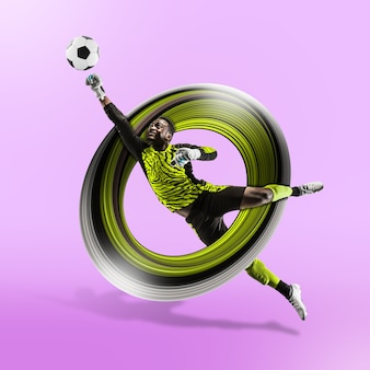Professional african american football or soccer player in motion isolated on purple studio background. fit jumping man in action, jump, play, excitement at game. abstract design, movement concept.