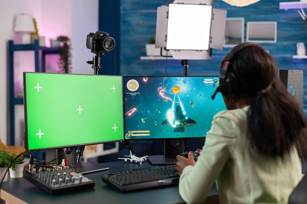 プロのアフリカのeスポーツ選手は、クロマキー付きのコンピューターを使用してチャンピオンシップをストリーミングします。グリーンスクリーンで分離されたデスクトップストリーミングスペースシューティングビデオゲームでpcを使用するゲーマー。
