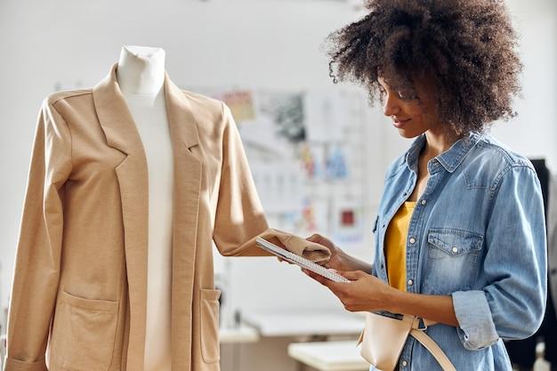ノートブックを持つプロのアフリカ系アメリカ人のファッションデザイナーは、ワークショップで新しいジャケットの袖をチェックします