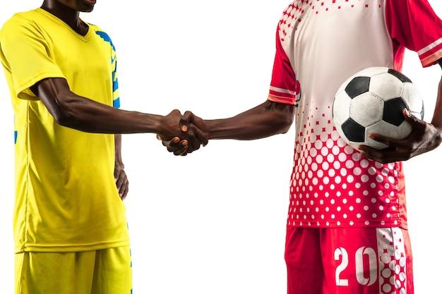 動いている黄色いチームのプロのアフリカ系アメリカ人のサッカーまたはサッカー選手