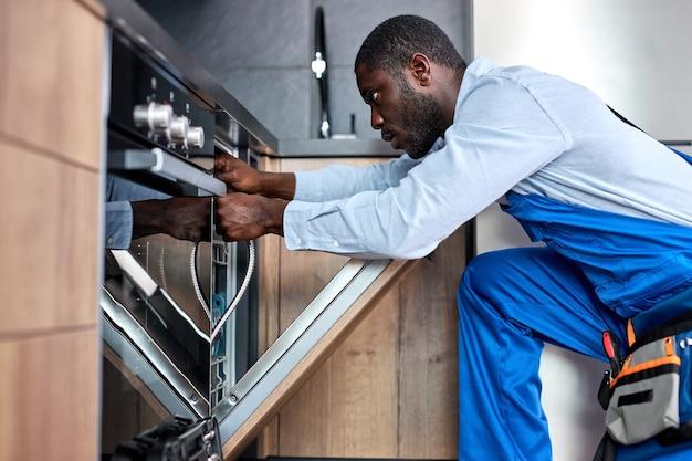プロのアフロ便利屋または請負業者が食器洗い機を修理し、古い食器洗い機のホースを交換する必要があります。青いオーバーオールの黒人の男は、屋内のキッチンで仕事に集中しています。側面図の肖像画。