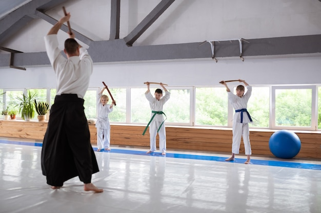 Профессиональный тренер по айкидо в униформе обучает талантливых детей