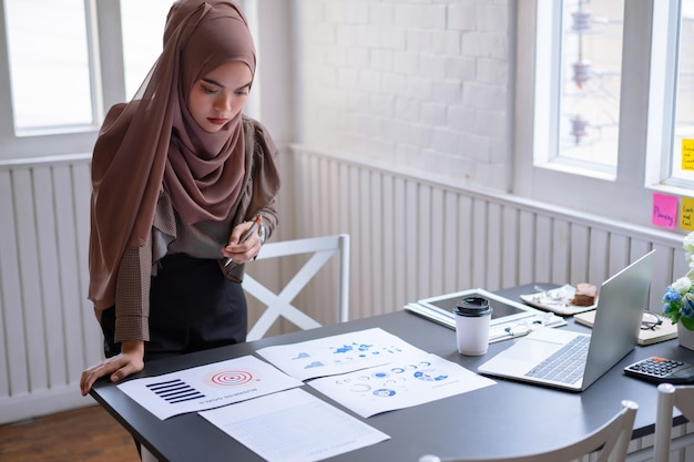 Professional arab businesswoman brown hijab standing and checking in financial investment project graph chart report.