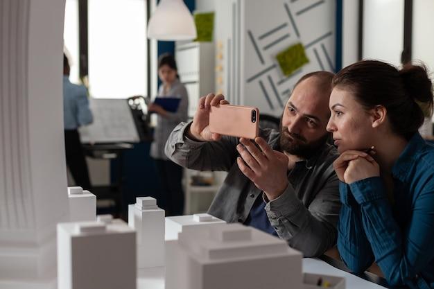 プロの建築家の同僚は、建物のモデルを見ながら机に座ってスマートフォンで作業します... Premium写真