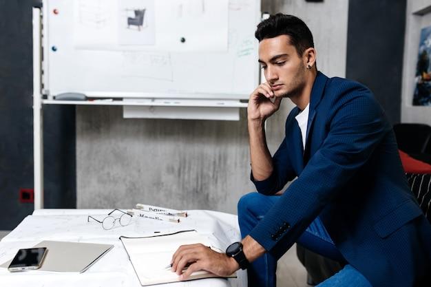세련된 옷을 입은 전문 건축가는 드로잉 자와 전화기가 있는 탁자 위의 공책에 메모를 합니다.