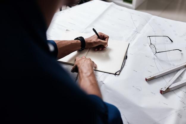 전문 건축가는 그림과 눈금자가 있는 탁자 위의 공책에 메모를 합니다.