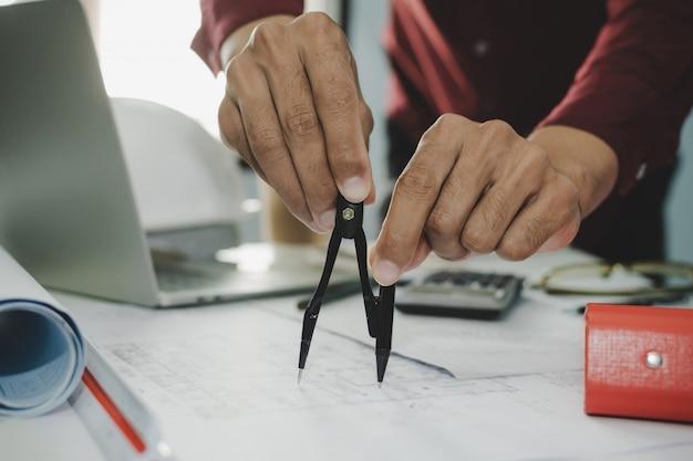 プロの建築家やインテリアデザイナーの手が建設現場、建設産業、エンジニアリングビジネスコンセプトの会議室オフィスの机の上の青写真にディバイダーコンパスで描く