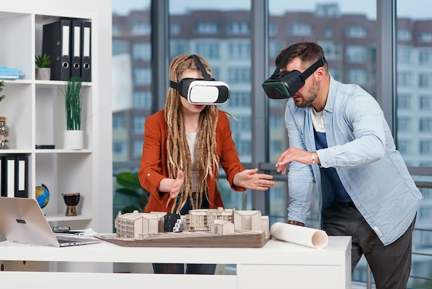 Профессиональный архитектор, работающий за офисным столом и одетый в гарнитуру vr, просматривает интерфейс виртуальной реальности.