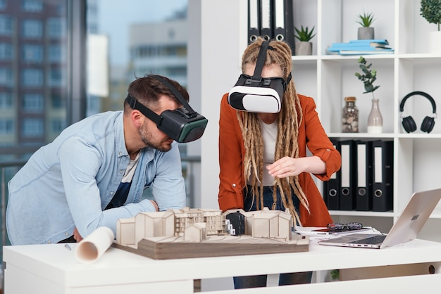 Professional architect working at office desk and wearing a vr headset, he is viewing a virtual reality interface