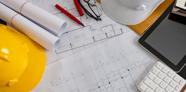 Professional architectural and engineering office desk with drawings and hard hat