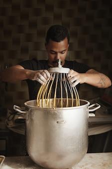 プロの職人菓子、黒人男性のチーフは、ブレンドされた卵と大きな鍋から大きな工業用泡立て器を取ります