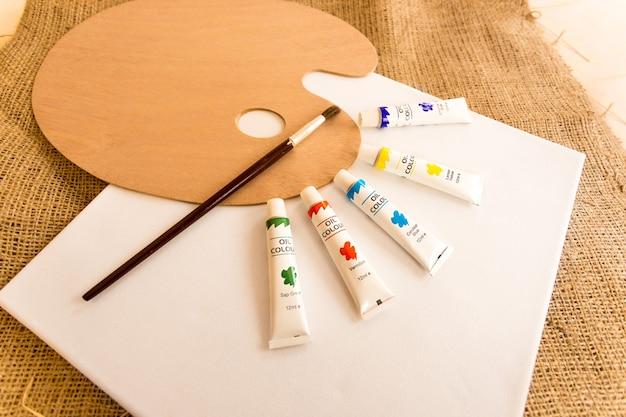 Инструменты профессионального художника, лежащие на столе, покрытом мешковиной