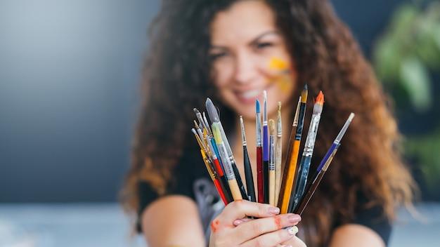 プロのアーティストツール。絵筆のセットを保持している巻き毛のブルネットの女性の肖像画。