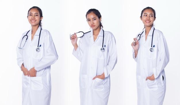ラボコートの制服を着た黒髪のプロのアジアの美しい医師の看護師の女性は、聴診器を持って医療病院でチェックして笑顔、白い背景のスタジオ照明、コラージュグループパックの肖像画