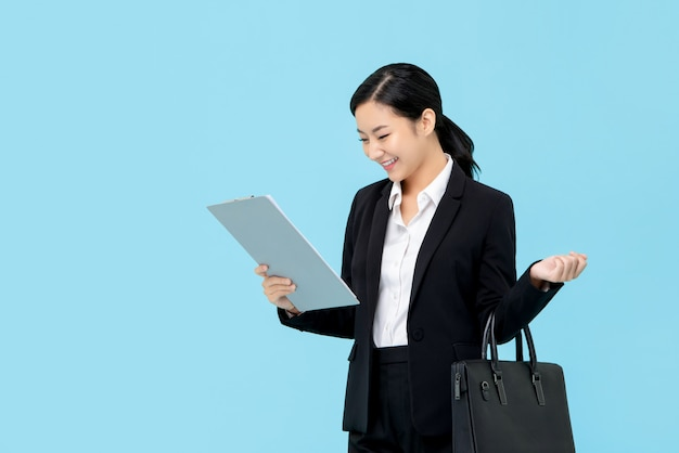 Professional asian businesswoman in formal suit looking at clipboard