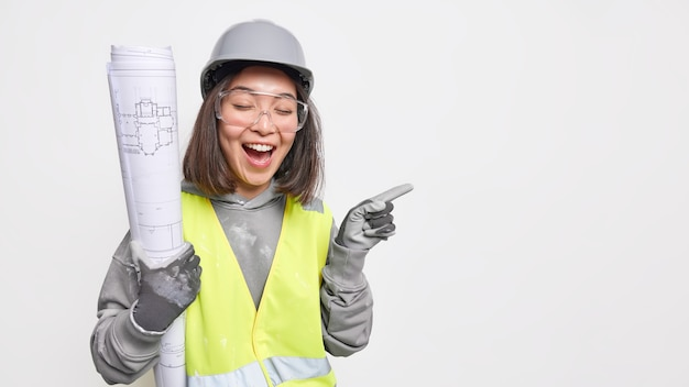 Professional asian female construction engineer inspects enterprise holds rolled blueprints wears uniform safety helmet and helmet laughs positively points on blank space over white wall
