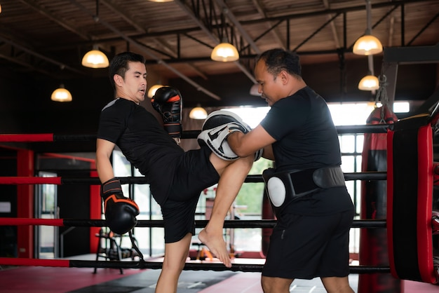 Professional asian kick boxer strike with the right knee to professional trainer in boxing stadium.