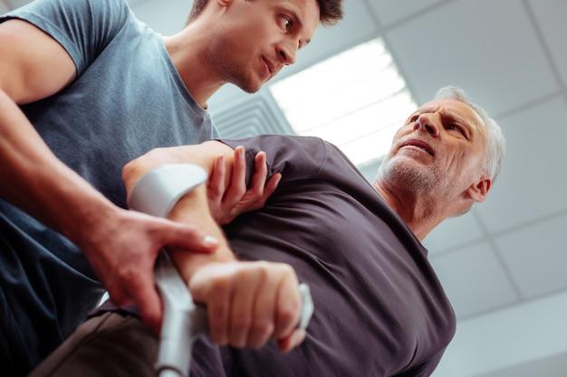 専門家による支援。彼が歩くのを手伝っている間彼の患者を見ている男性看護師のローアングル