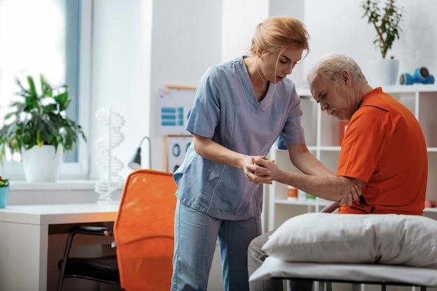 전문적인 지원. 그의 손을 잡고 그녀의 환자 침대 위에 서있는 전문 여성 간호사