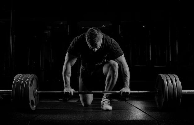 Профессиональный спортсмен наклонился над штангой и готовится поднять очень тяжелый вес. передний план