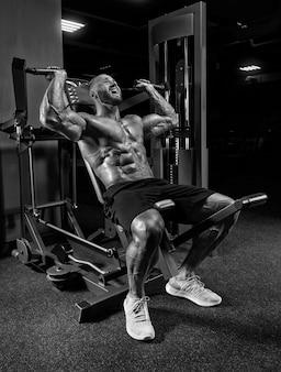 Профессиональный спортсмен делает тренировку плеч в тренажерном зале. бодибилдинг, фитнес, спортивная концепция. смешанная техника