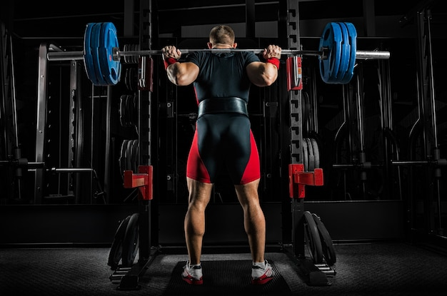 Professional athlete is standing with a barbell on his shoulders and is about to sit down with her. view from the back.