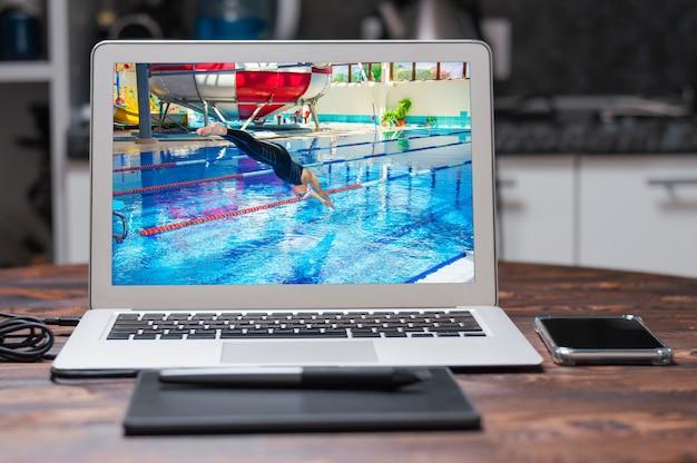 Профессиональный спортсмен прыгает в воду в бассейне с платформы