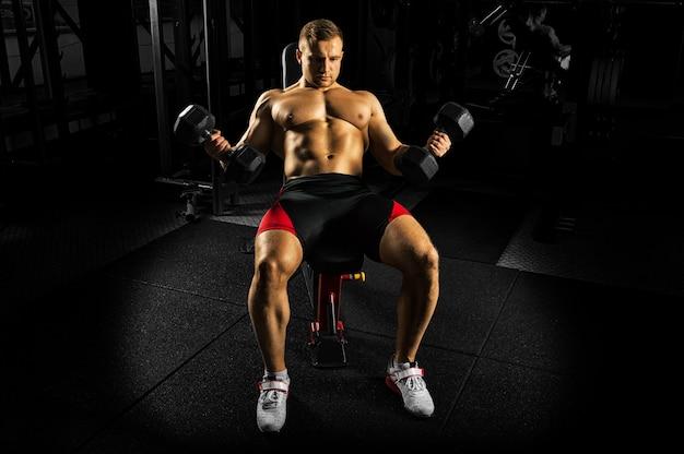 프로 운동 선수는 벤치에 앉아 덤벨을 들어 팔뚝 운동을합니다.