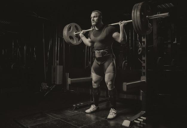 Профессиональный спортсмен делает приседания со штангой в тренажерном зале