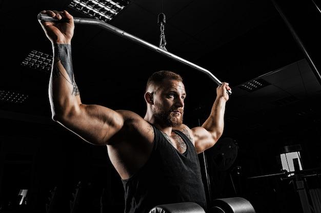 Профессиональный спортсмен выполняет упражнение в тренажерном зале. подтягивает штангу к затылку. упражнение на развитие мышц спины
