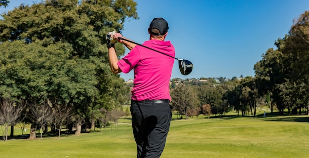 暖かい晴れた日にゴルフをするプロスポーツ選手