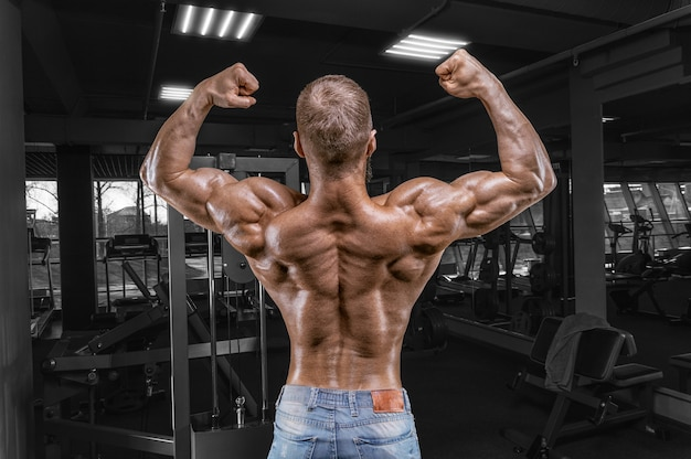 Professional athlete posing in the gym. back view. bodybuilding and fitness concept.