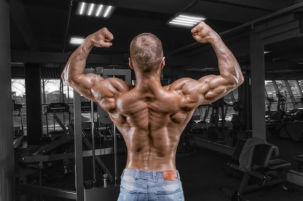 Профессиональный спортсмен позирует в тренажерном зале. вид сзади. бодибилдинг и фитнес-концепция. Premium Фотографии