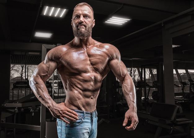 Профессиональный спортсмен позирует в тренажерном зале. бодибилдинг и фитнес-концепция.