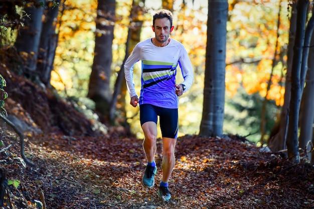 Профессиональный бегун-спортсмен тренируется среди листьев в лесу