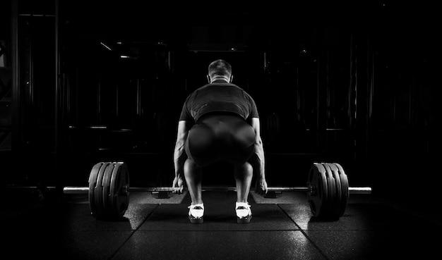Профессиональный спортсмен сидит перед штангой и готовится ее поднять. вид сзади