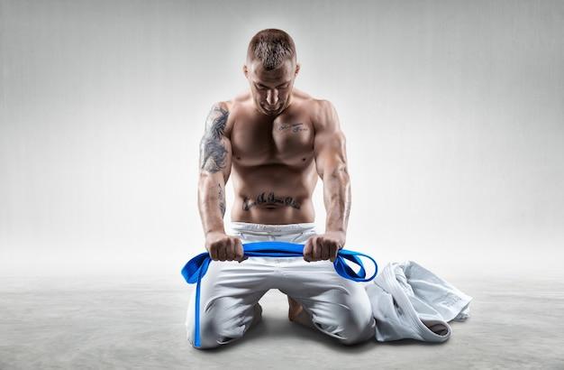 プロスポーツ選手は、青いベルトの着物を着てジムに座っています。空手、柔術、サンボ、柔道のコンセプト。ミクストメディア