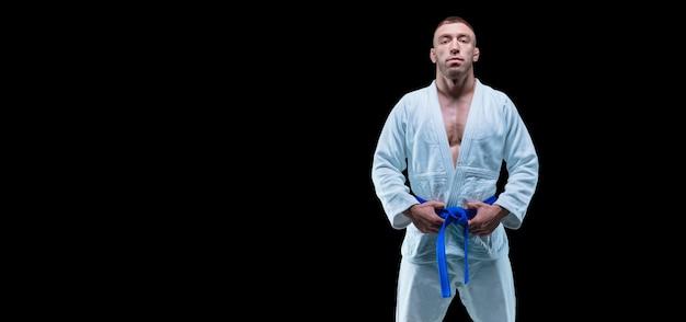 プロスポーツ選手が青い帯の着物を着てジムに立っています。空手、柔術、サンボ、柔道のコンセプト。ミクストメディア