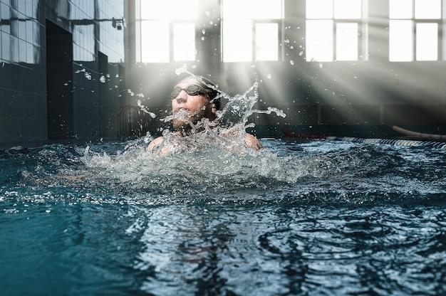 Профессиональный спортсмен плывет брассом в бассейне