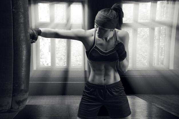 Профессиональный спортсмен тренирует удар по сумке в тренажерном зале