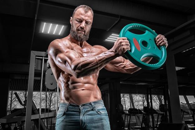 Профессиональный спортсмен тренируется со штангой в тренажерном зале. бодибилдинг и фитнес-концепция.