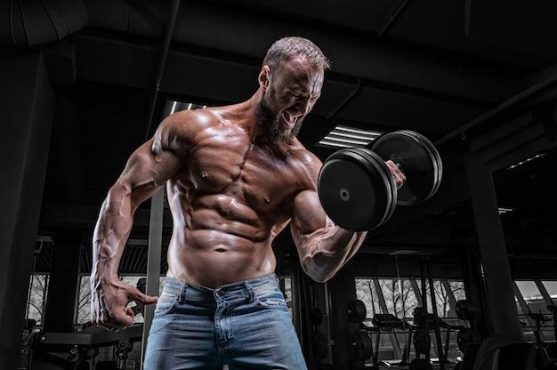 Профессиональный спортсмен тренируется с гантелями в тренажерном зале. прокачка бицепса. бодибилдинг и фитнес-концепция. Premium Фотографии