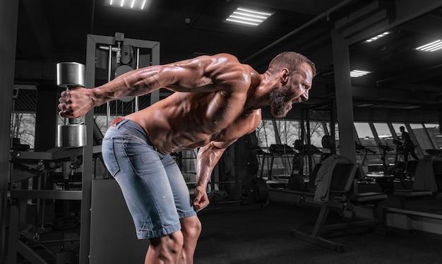 Профессиональный спортсмен тренируется с гантелями в тренажерном зале. прокачка трицепса. бодибилдинг и фитнес-концепция.