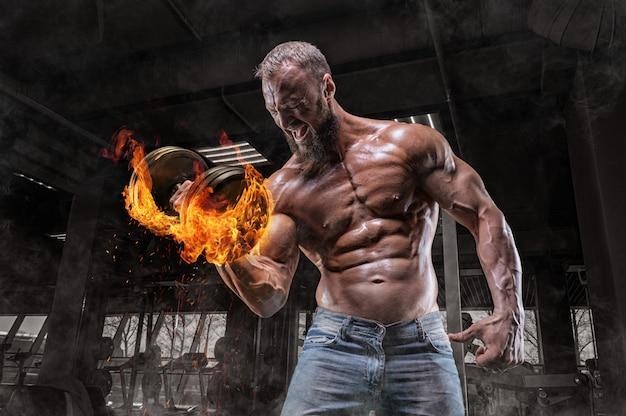 Профессиональный спортсмен тренируется с огненной гантелью в тренажерном зале. прокачка бицепса. бодибилдинг и фитнес-концепция. Premium Фотографии